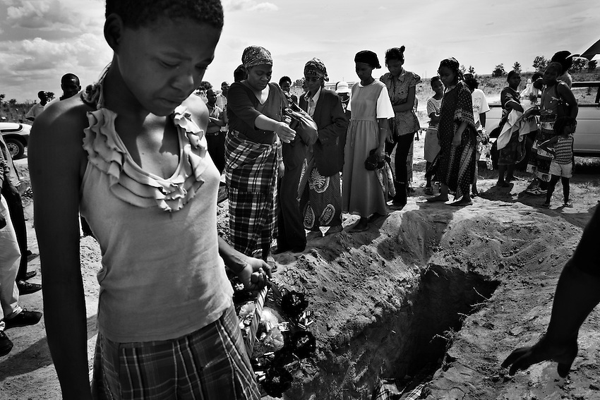A young Zimbabwean girl cries at the funeral of her grandmother, Emmely Munyonga (74), who died of cholera and is being buried in the B wing of Granaville Cemetary, which has been designated for cholera victims, near Budiriro, Zimbabwe, Sunday, December 14, 2008.