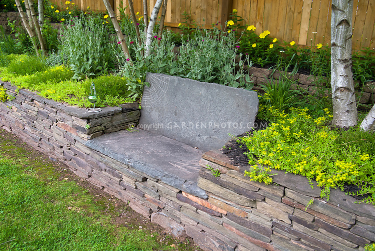 etched artistic stone garden bench in raised bed stone wall fence birch trees