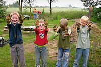 Lehmbackofen im Schulgarten, Garten der Grundschule Nusse wird als Projektarbeit von einer 1. Klasse gestaltet, Kinder bringen feuchten Lehm an einem Lehmbackofen an und zeigen begeistert ihre lehmigen Hände, Gartenarbeit