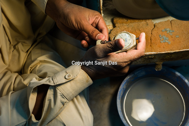 A worker measures a gem stone while polishing fine jewelry at the workshop at The Gem Palace in Jaipur, Rajasthan, India.