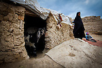 """Kartenow - Nasaji Bagramy, District 8- IDP Camp, Eastern Kabul is home to 360 families, 2500 people-  mainly from Helmand. Saber Bibi, 15, did not want to be photographed- originally from Kandahar but went to marry her husband in Lashkar Gar, Helmand and had to flee because of the conflict.<br /> Came to the camp three years ago.<br /> toddler son Talib Jan, 2<br /> """"My baby Fatima was born but after 10 nights she died. I don't know what the sickness was but the baby was normal."""" The birth at her mother's home was at full term and when she came back to the camp a month ago she got sick.<br /> """"How could I keep my baby warm in this house? Maybe she froze to death, I think that's how she died.""""<br /> Talib, his face covered in dirt, in a grubby coat and red wellies is holding a bag of pills, medicine for his grandmother, but he's not giving it back and he starts to eat them.<br /> Cracked mud walls and floor with open draught through the door.<br /> """"We came here because of the conflict. We have to buy water<br /> Has bare feet in sandals despite the cold – the next morning Kabul is coated in snow.<br /> """"We were poor even before coming here. My father was a labourer and didn't have a proper job. """"Then because of the conflict we left. There were bombings in the area and we lost so many people.<br /> Nervous to leave the hut and becomes agitated when men come near the door, pulling her scarf tighter. """"Even my brother-in-law hasn't seen my face.""""<br /> Beautiful auburn curly hair and kohled eyes.<br /> """"I've not been to school but I've attended tailoring classes. I'd like to work but only if it's nearby. My husband will not allow me to leave the camp. If these people training us belong to the camp my husband doesn't have a problem.""""<br /> """"We are poor. Our husbands work but we are just sitting in our house idle. I'd like to work but I'm not allowed.<br /> """"We eat whenever it's available. We don't usually eat three times a day and when we do it's oninons with bread.<br /"""