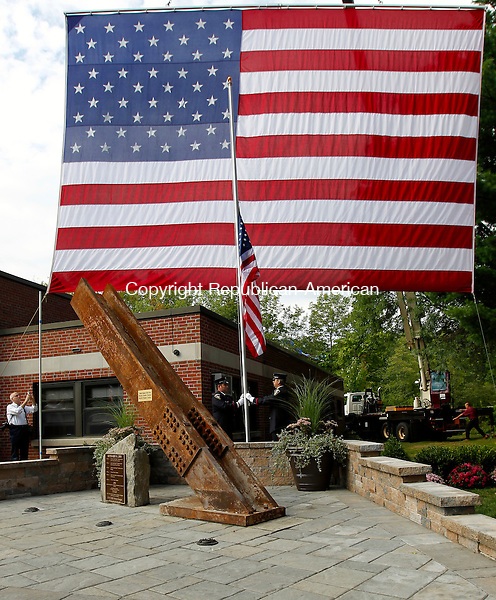 Torrington, CT- 11, September 2011-091111CM10 Torrington firefighters Robert Ebner (left) and Jeremy Minard raise the American Flag as the 9/11 Memorial is unveiled at the North End Fire Station in Torrington Sunday morning.   This beam came from the World Trade Center North Lobby and will be displayed  as a memorial outside of the fire station.  Christopher Massa Republican-American