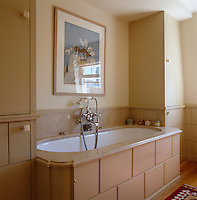 The bath in this contemporary bathroom has a marble splashback and surround and is encased in a wooden frame
