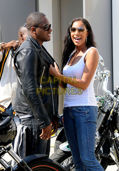 TAIO CRUZ & SU-ELISE NASH .At the Harley Davidson Celebrity bike ride, Warr's Harley Davidson, Kings Road, London, England, UK, .9th August 2009..half length white vest top jeans black biker leather jacket sunglasses shades profile .CAP/CAN.©Can Nguyen/Capital Pictures