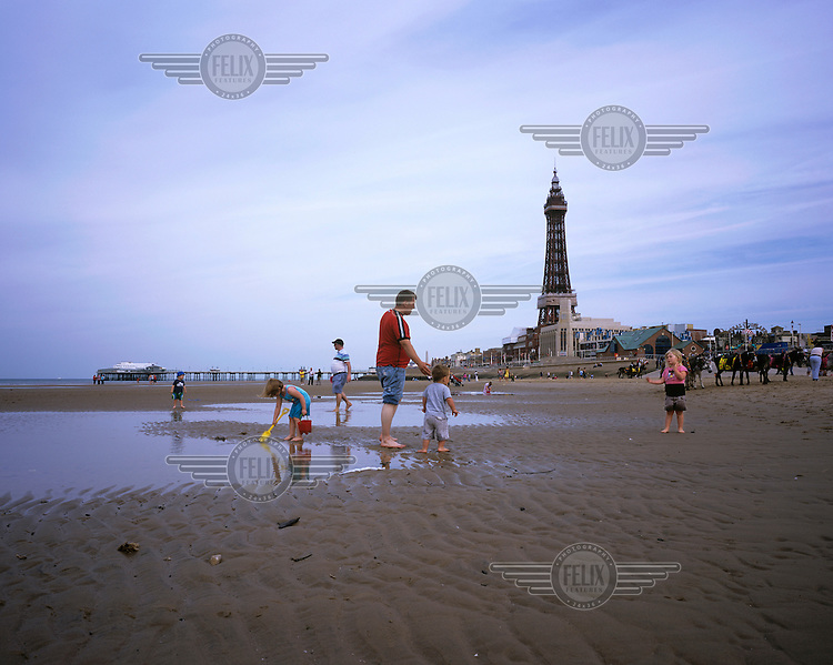 A family play on the beach near Blackpool Tower and North Pier.