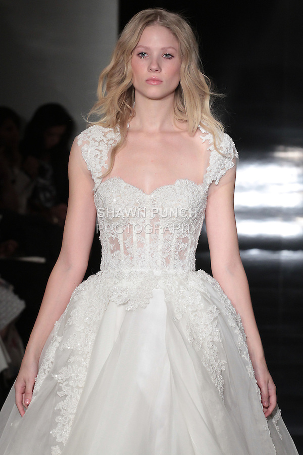 Model walks runway in a silk organza gown with re-embroidered lace corset and embroidered detachable overskirt and detachable shoulder wrap, from the Reem Acra Spring 2017 bridal collection, during New York Bridal Fashion Week Spring Summer 2017, on April 15, 2016.