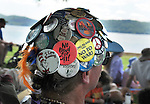 "Button covered cap of one of the members of audience watching the Arm-of-the-Sea Theater performance of the play, ""CITY that DRINKS the MOUNTAIN SKY,"" performed at the edge of the Hudson River during the 2012 Clearwater Festival at Croton Point Park on Saturday, June 16, 2012. Photograph taken by Jim Peppler. Copyright Jim Peppler/2012"