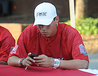 Wilmer Flores of the Savannah Sand Gnats checks his messages at the 2010 South Atlantic League All-Star Game welcome party and festivities Monday night June 21, 2010, at the Wyche Pavilion along the Reedy River in Greenville, S.C. Photo by: Tom Priddy/Four Seam Images