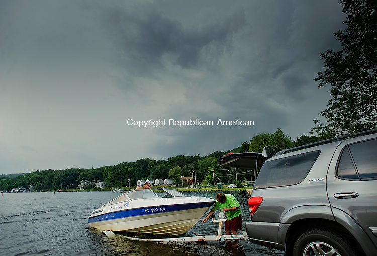WINSTED, CT-18 JULY 2012--071812JS02-Ross Mainville, left, and Tony Stapelfeld, both of Canton, work on getting Mainville's boat onto the trailer at the dock at Highland Lake as a thunderstorm rolls in to the Winsted area on Wednesday afternoon. .Jim Shannon Republican-American