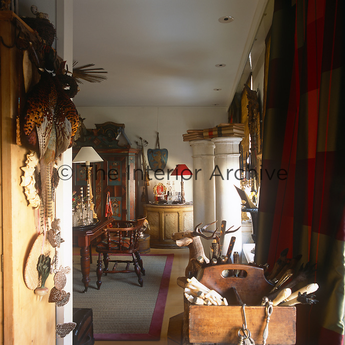A view into a room with antiques and other items arranged as though in an antiques shop.