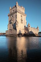 The Torre de Belem or Belem Tower, built in the 16th century by Francisco de Arruda under King John II as part of a defence system at the mouth of the river Tagus and a ceremonial gateway to the city, Santa Maria de Belem, Lisbon, Portugal. The limestone tower is built in Late Gothic Manueline style, and consists of a bastion terrace (right), 4 storey tower and small access bridge. It is listed as a UNESCO World Heritage Site due to its important role during the Portuguese Age of Discoveries. Picture by Manuel Cohen