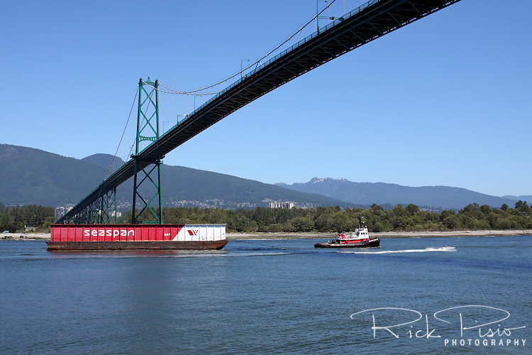 A tugboat pulls a barge under Vancouver's Lions Gate Bridge