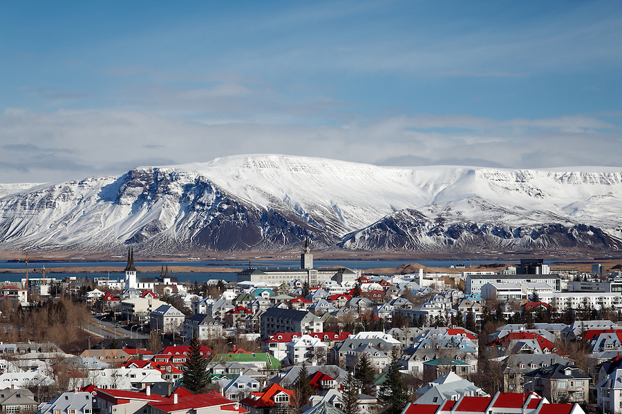Snowy Kambshorn mountain towering above Reykjavik city skyline, Iceland