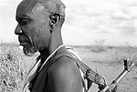 A Turkana man and automatic weapon in a traditional village nr Kakuma, Northern Kenya.<br /> He uses his gun as protection against marauding tribes  that come and steal his livestock.<br /> With the high amount of unrest in the region there has been a proliferaiton of weapons and a Kalashnikov can be  bought for as little as $10 USD.
