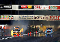 Nov 15, 2014; Pomona, CA, USA; NHRA funny car driver Jon Capps (left) explodes an engine on fire alongside Jeff Diehl during qualifying for the Auto Club Finals at Auto Club Raceway at Pomona. Mandatory Credit: Mark J. Rebilas-USA TODAY Sports