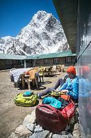 A trekker at a Nepali guesthouse organizes her duffel bags, with the mountain Cholatse above, Dzongla, Nepal.