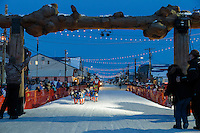 Alan Eischens runs into the finish chute and under the burl arch in Nome on Saturday March 21, 2015 during Iditarod 2015.  <br /> <br /> (C) Jeff Schultz/SchultzPhoto.com - ALL RIGHTS RESERVED<br />  DUPLICATION  PROHIBITED  WITHOUT  PERMISSION