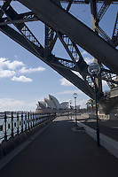 The famous Opera House in Sydney, Australia,  seen from under the south end of the Harbour Bridge. These two iconic buildings, standing almost side by side, are both symbols of national identity.
