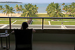 Woman relaxing on hotel balcony, Amaya Beach Resort hotel, Pasikudah bay, Eastern Province, Sri Lanka
