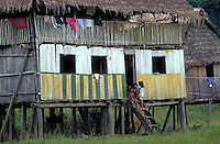 Children in front of wooden house in Amazonian region of Peru