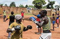 The Peace for Children Africa (PCA) drop in centre for street children. The centre, which is situated on the edge of the Kisenyi slums, hosts meals, courses and activities for street children to begin a process of rehabilitating them. 4-5-15 Boys are coached in boxing skills at the centre.