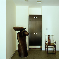 A bronze sculpture by Keping stands beside a Chinese armchair in a corner of the living room