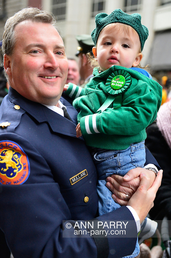 """March 16, 2013 - New York, NY, U.S. - Nassau County Police Officer holidng young boy in green who's wearing """"Get Luck Be Irish"""" button, shortly before marching in the 252nd annual NYC St. Patrick's Day Parade."""