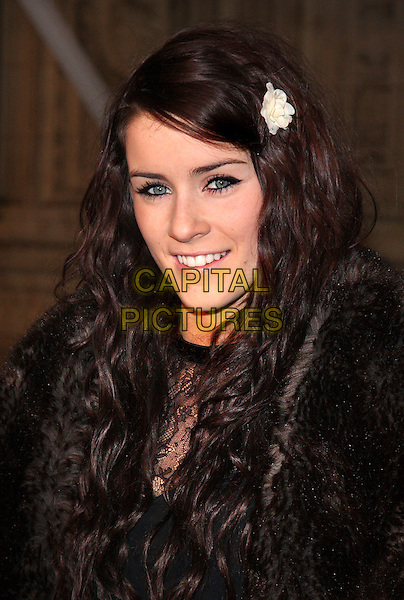 LUCIE JONES .Attending the Gala VIP Opening Night of Cirque du Soleil's 'Varekai' at the Royal Albert Hall, London, England, UK, .January 5th 2010..arrivals portrait headshot smiling black make-up eyeliner flower in hair clip accessory white cream fur wavy bad skin spot spots .CAP/ROS.©Steve Ross/Capital Pictures.