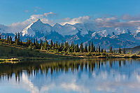 Alaska range mountains, including Mt Brooks, reflect in the still morning water of Wonder Lake, Denali National Park, interior, Alaska.