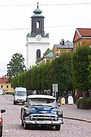 Street scene with an old American Chevrolet car from the 1950s. The church in the background. Eksjo town. Smaland region. Sweden, Europe.