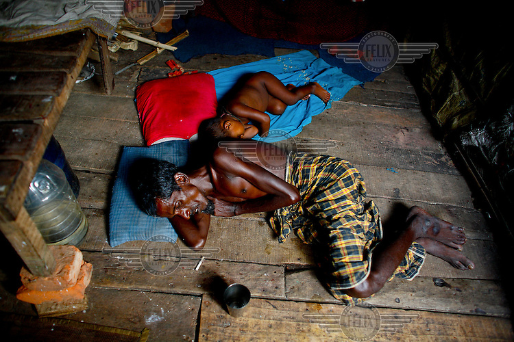 A man sleeps with his baby on the bare floor of their home in one of the city's slum districts. It is thought that more than six million people live in slums in Dhaka.