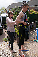 April 30th 2020, NEWCASTLE-UNDER-LYME, United Kingdom; British triathlete Lloyd Bebbington is helped into his wetsuit by his mother Marie before training in a temporary swimming pool in his garden because of the coronavirus lockdown restrictions in Newcastle-under-Lyme