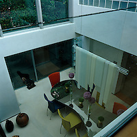 A view looking down to the double-height dining room furnished with a Ron Arad table surrounded by multi-coloured chairs