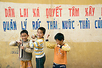 "Vietnam. Ha Tay province. Lai Xa. Three young boys smile, laugh and show their arms' muscles. On the wall, a painted slogan is writen in vietnamese language. "" The local government and the Lai Xa community have sucessfully built the progress on sanitation of solid-waste and waste-water "".  Through the construction of a main drainage and the building of sewerage as a combined system, collecting both rainwater and domestic waste water, the implementation of a flexible decentralized community sanitation project in a context of low infrastructure investment and in a peri-urban case study, such as Lai Xa, is a major sucesss. It offers importants benefits as an alternative to centralized systems, namely in terms of health improvements and by the possibility of dealing with wastewater locally, through households and decentralized municipal structures. Lai Xa is a typical hamlet (village) of the Red River delta region and is part of the Kim Chung commune located 15 km west of Hanoi. This peri-urban location is under increasing pressure from the forces of urbanization. 06.04.09  © 2009 Didier Ruef"