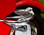 With her beautiful flowing lines, the silver Flying Lady hood ornament is reflected in the grill of a fire-engne red, 1932 Plymouth at the 2010 Wings 'n' Wheels Showcase, Galway, New York.