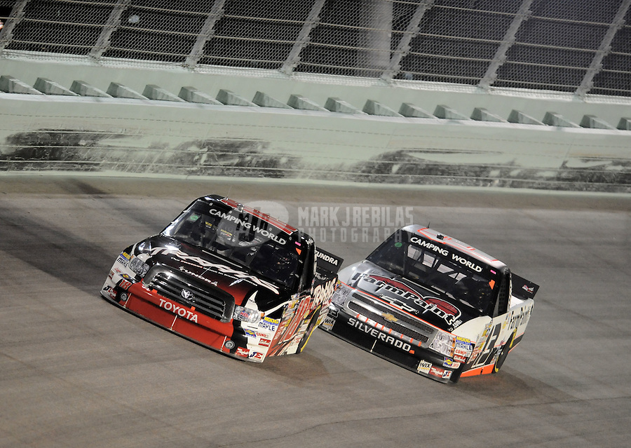 Nov. 19, 2010; Homestead, FL, USA; NASCAR Camping World Truck Series driver Kyle Busch (18) leads Johnny Sauter (13) during the Ford 200 at Homestead Miami Speedway. Mandatory Credit: Mark J. Rebilas-