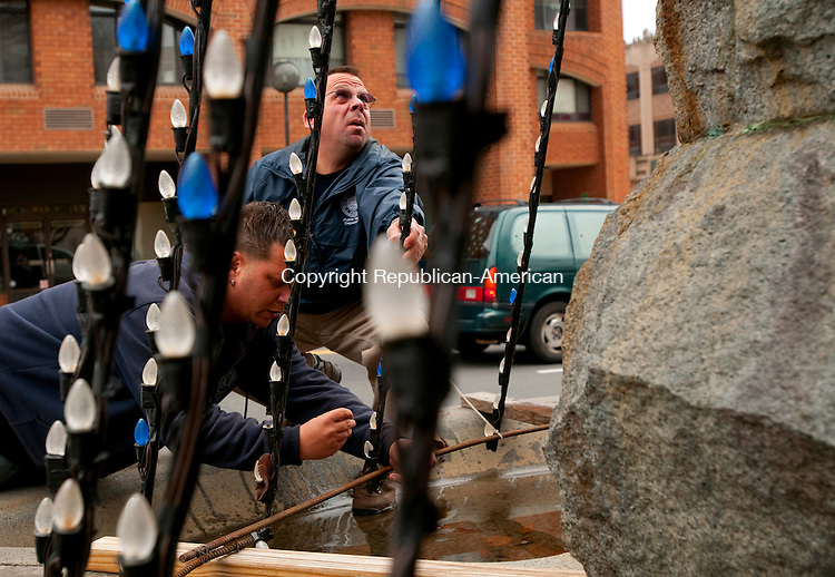 WATERBURY, CT, 15 NOVEMBER 2010-111510JS04--Anthony Piccochi, Jr., left, and Bob Gaetano, right, both with the Waterbury Public Works Parks department, install Christmas lights around the fountain at the bass horse statue in the Green in Waterbury on Monday. <br />  Jim Shannon Republican-American