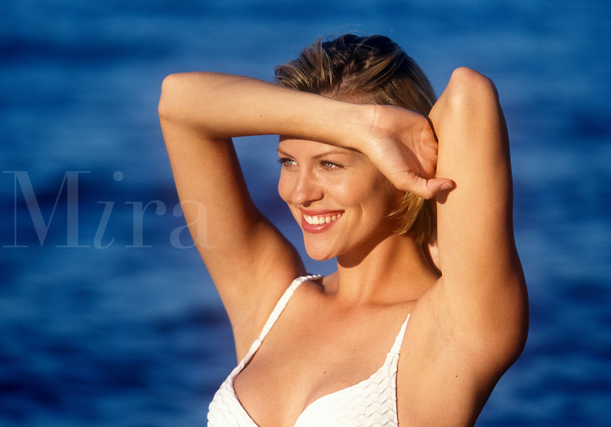 Attractive woman posing in a bathing suit by the water.