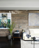 One wall of the living room is clad with planks of reclaimed wood from an old barn; the photograph is by Jackie Nickerson and the painting by Carlos Vega