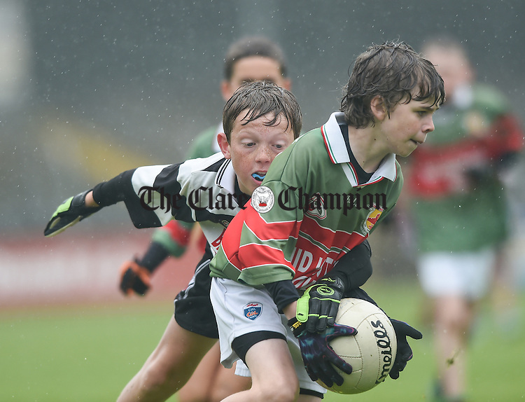 Fiachra Hale of Clooney-Quin in action against Clarecastle's Conor Whelan during the U-12 football finals in Cusack park. Photograph by John Kelly.