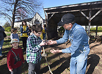 NWA Democrat-Gazette/FLIP PUTTHOFF <br /> BLACKSMITH AT WORK<br /> Owen Whitaker, 12, looks at chunks of coal Saturday March 18 2017 with blacksmith Joe Doster of Huntsville. Doster burned coal in his forge during his blacksmith demonstration Saturday at the Shiloh Museum of Ozark History in Springdale. He made nails and tools during his presentation and showed tools of the blacksmith's trade.