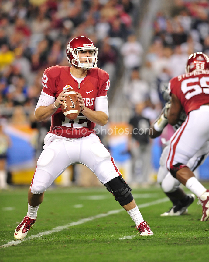 Jan 1, 2011; Glendale, AZ, USA; Oklahoma Sooners quarterback Landry Jones (12) pump-fakes a throw in the 4th quarter of the 2011 Fiesta Bowl against the Connecticut Huskies at University of Phoenix Stadium.  The Sooners won the game 48-20.