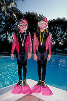 Twins in wetsuits, snorkels and flippers standing by a pool. Key Largo.