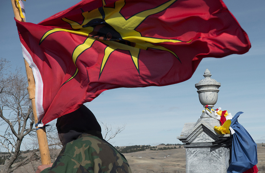 An American Indian Movement member holding the Lakota flag at the Wounded Knee memorial during the 40th anniversary of the occupation of Wounded Knee.In the Rezervation the men who participated in the Wounded Knee standing to fight for indipendence are also consider as  veterans and honored in a annual veteran pow wow.