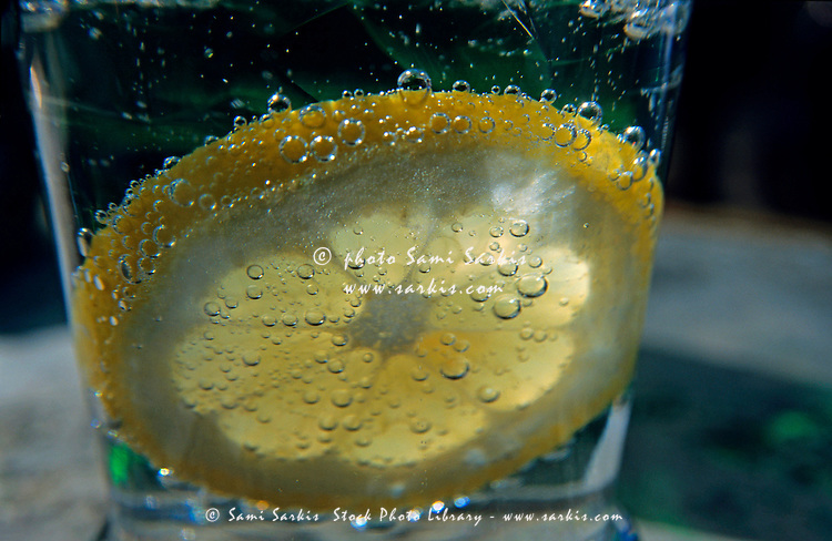 Lemon slice floating in a fizzy drink.
