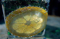 Lemon slice floating in a fizzy drink.