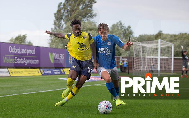 Tariqe Fosu of Oxford United battles Alex Woodyard of Peterborough United during the Sky Bet League 1 match between Oxford United and Peterborough at the Kassam Stadium, Oxford, England on 10 August 2019. Photo by Andy Rowland.