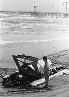 Beachgoers check out a partially buried junk car deposited on the beach by a noreaster storm , Daytona Beach, FL, December, 1984. (Photo by Brian Cleary/www.bcpix.com)