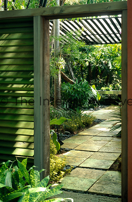 Entrance way into garden with coral limestone paving and green wooden louvre wall