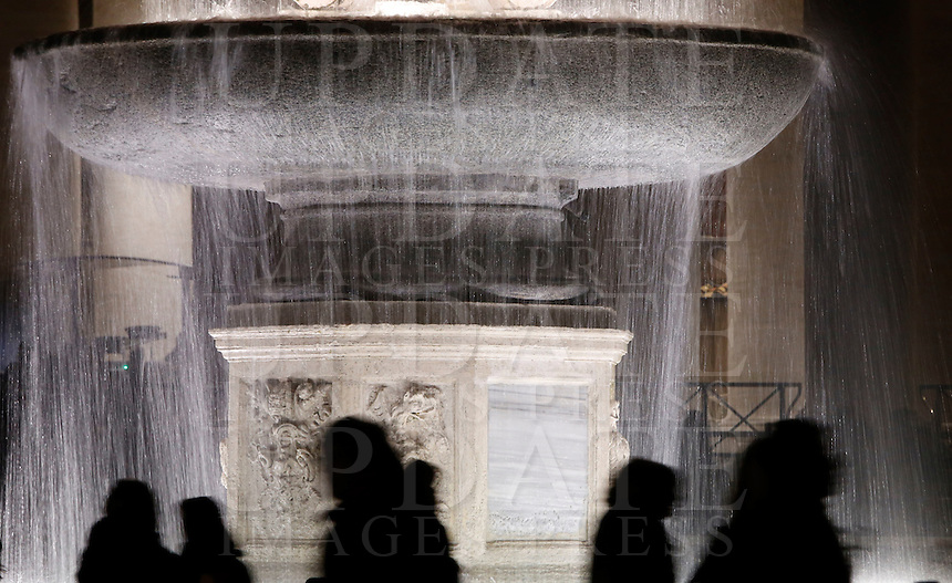 Turisti davanti a una delle fontane di Piazza San Pietro, Citta' del Vaticano, 6 dicembre 2015.<br /> Tourists pass past one of the fountains in St. Peter's Square at the Vatican, 6 December 2015.<br /> UPDATE IMAGES PRESS/Riccardo De Luca<br /> <br /> STRICTLY ONLY FOR EDITORIAL USE